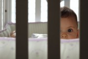 baby peering through crib slats
