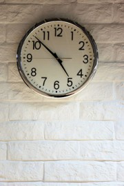 clock on a white brick wall