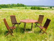 folding table and chairs in a meadow