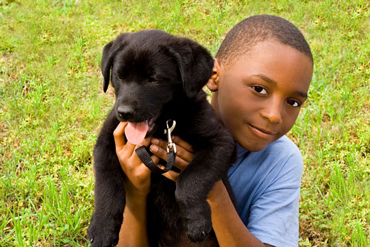 young black man with black pet dog